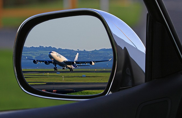 reflection of airplane taking off in car wing mirror
