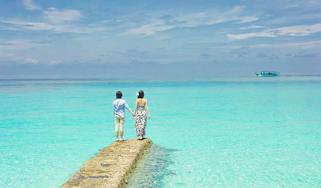 Young dating couple holding hands in Asian seascape