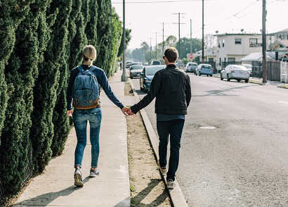 Young American couple holding hands in a public street