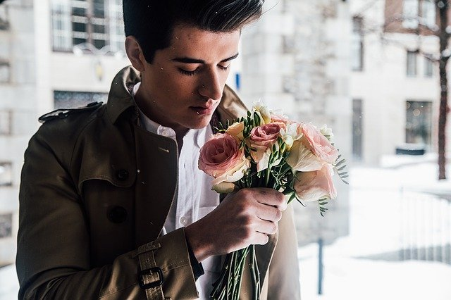 Romantic man in leather jacket and holding roses.