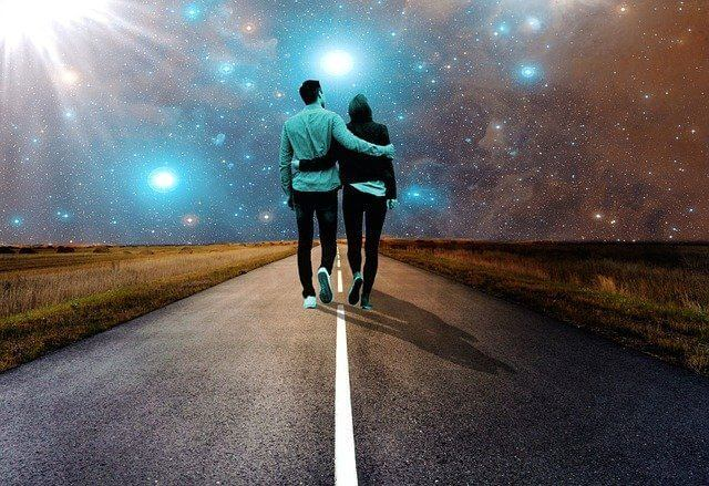 Young couple looking at stars while walking along a road at night - find me a partner